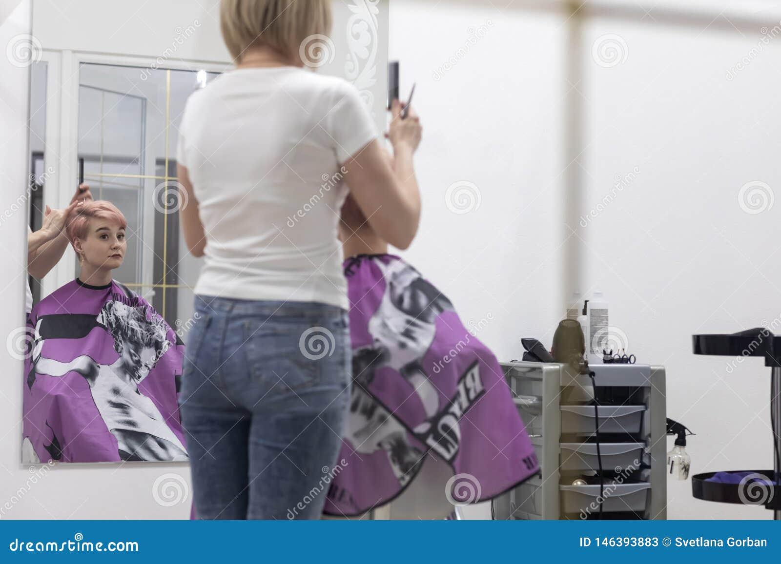 De vrouwenkapper maakt kapsel in een schoonheidssalon
