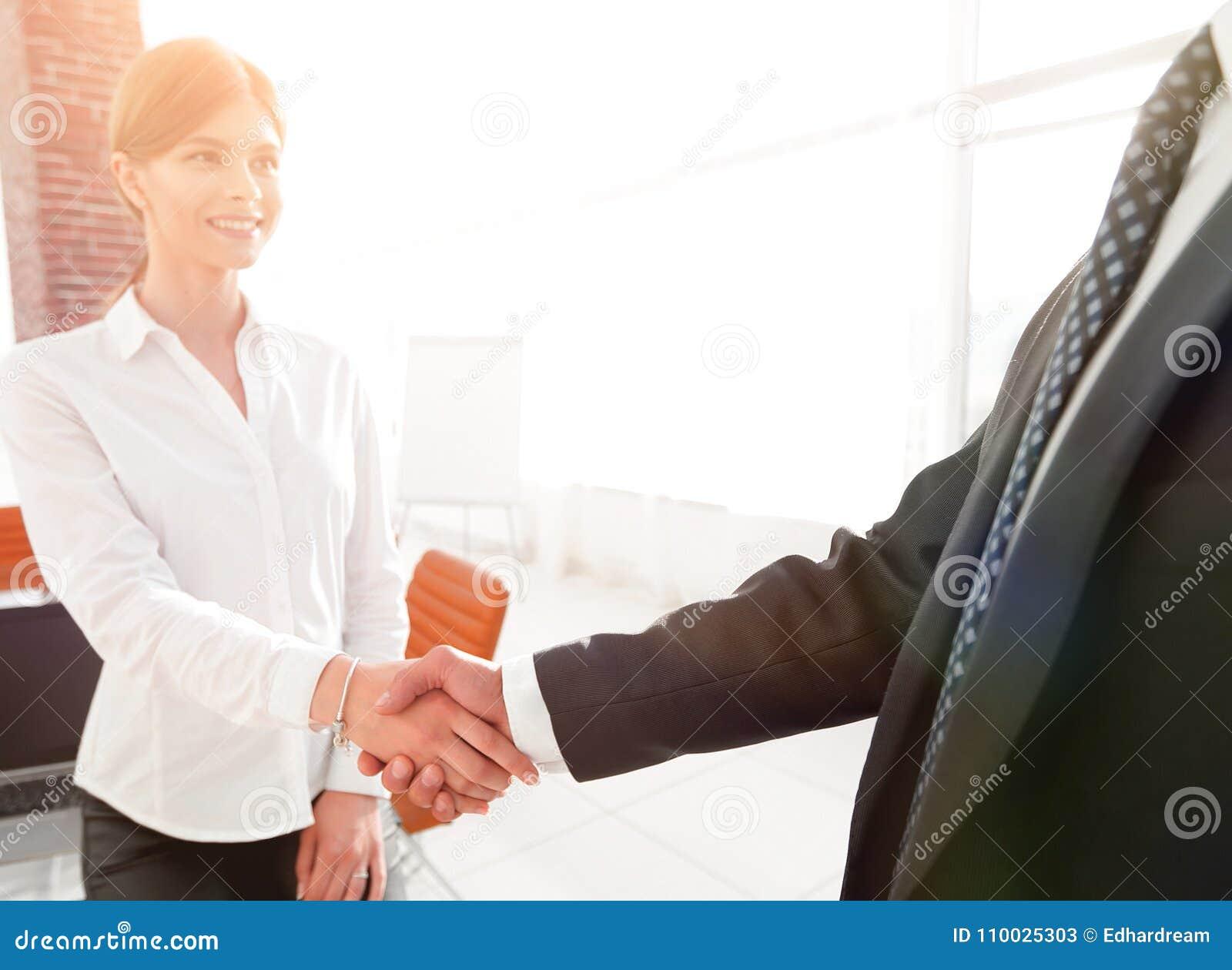 De vrouwenmanager heet de cliënt met een handdruk welkom