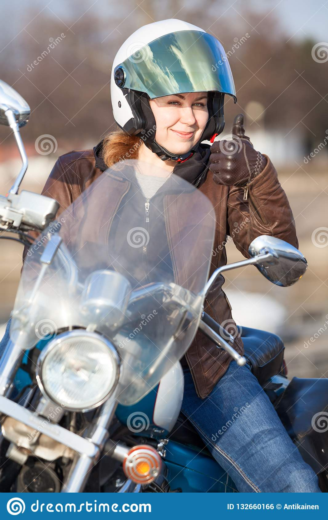 De vrouwenmotorrijder in bruin leerjasje en de witte veiligheidshelm die duim tonen ondertekenen omhoog met hand
