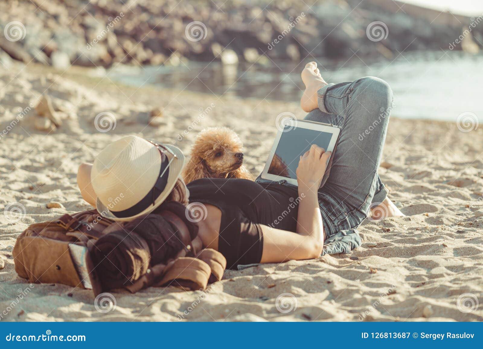 De vrouwenreiziger houdt aanrakingsstootkussen, terwijl in openlucht tijdens zijn reis op het overzees ontspant