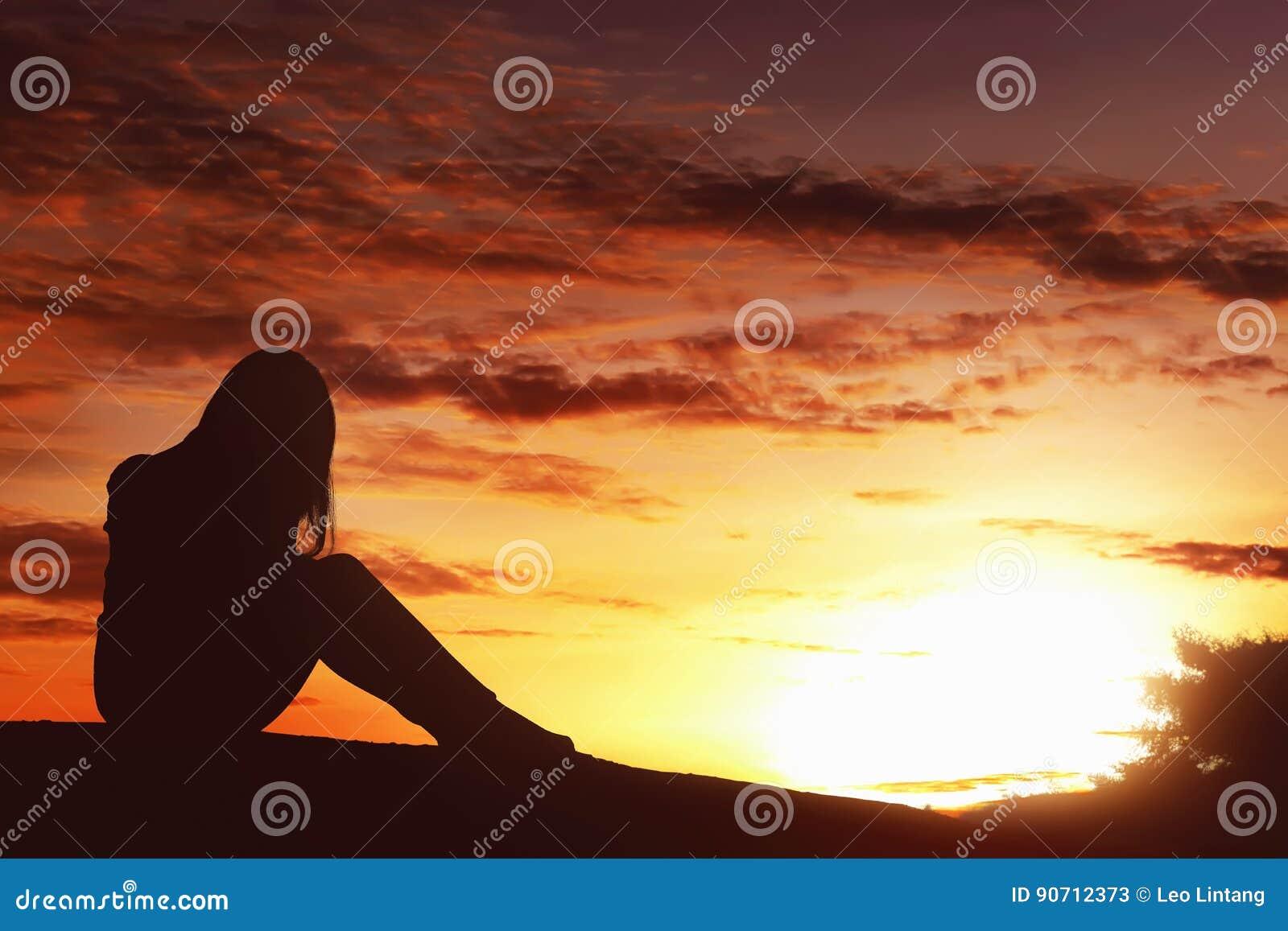 De vrouwenzitting van de silhouet droevige uitdrukking alleen bovenop de heuvel