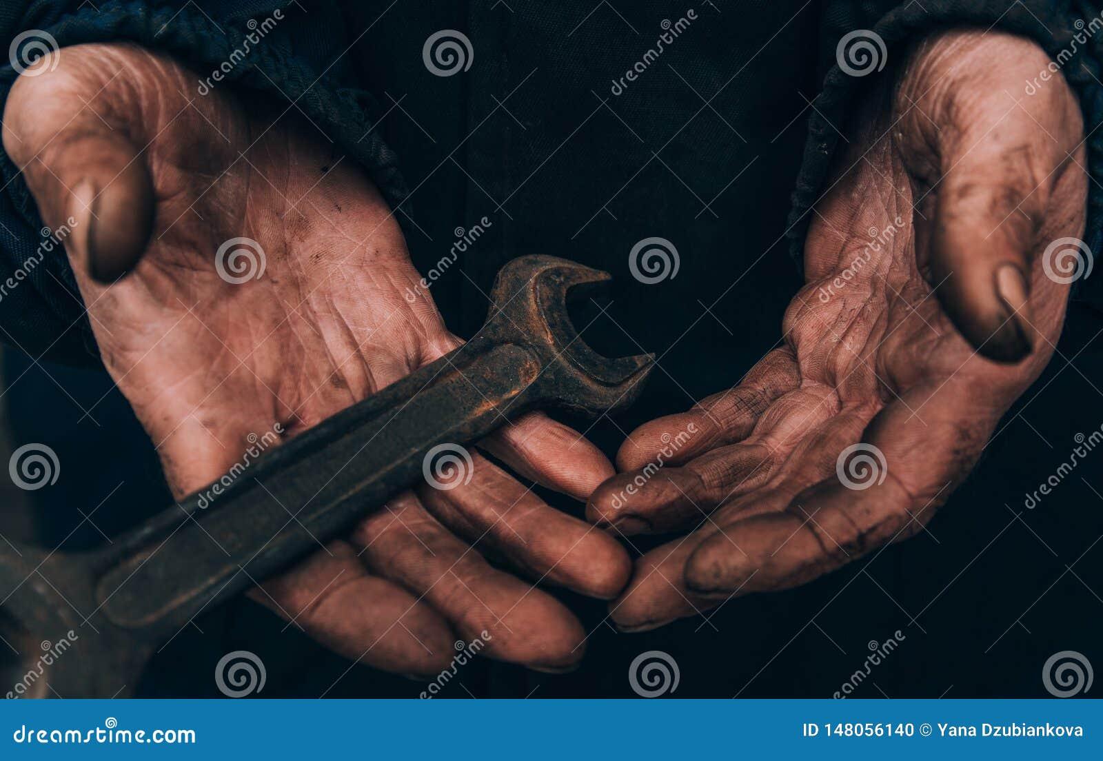 De vuile handen van een mens, een werkende mens, een mens voerden zijn handen af terwijl het werken, een slechte mens