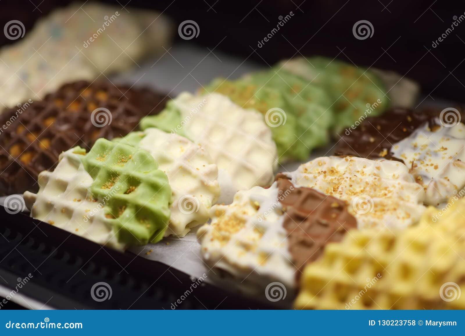 De wafels van Belg en van Luik met chocolade, bessen, zoete saus, room in het venster van een koffie of opslag