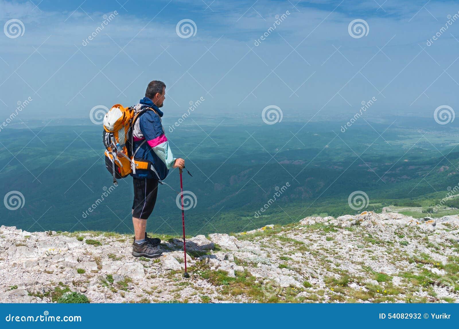 De wandelaar bewondert het landschap van de de lentebergen