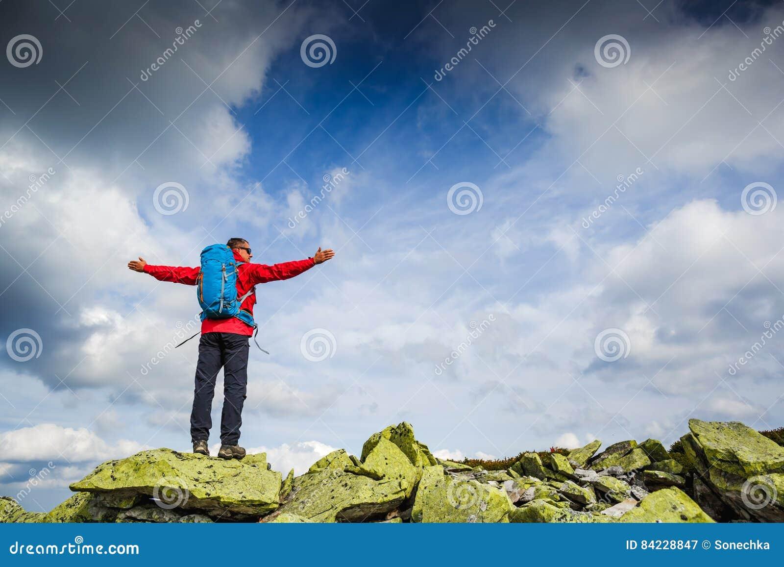 De wandelaar bij de bovenkant van een rots met rugzak geniet van zonnige dag