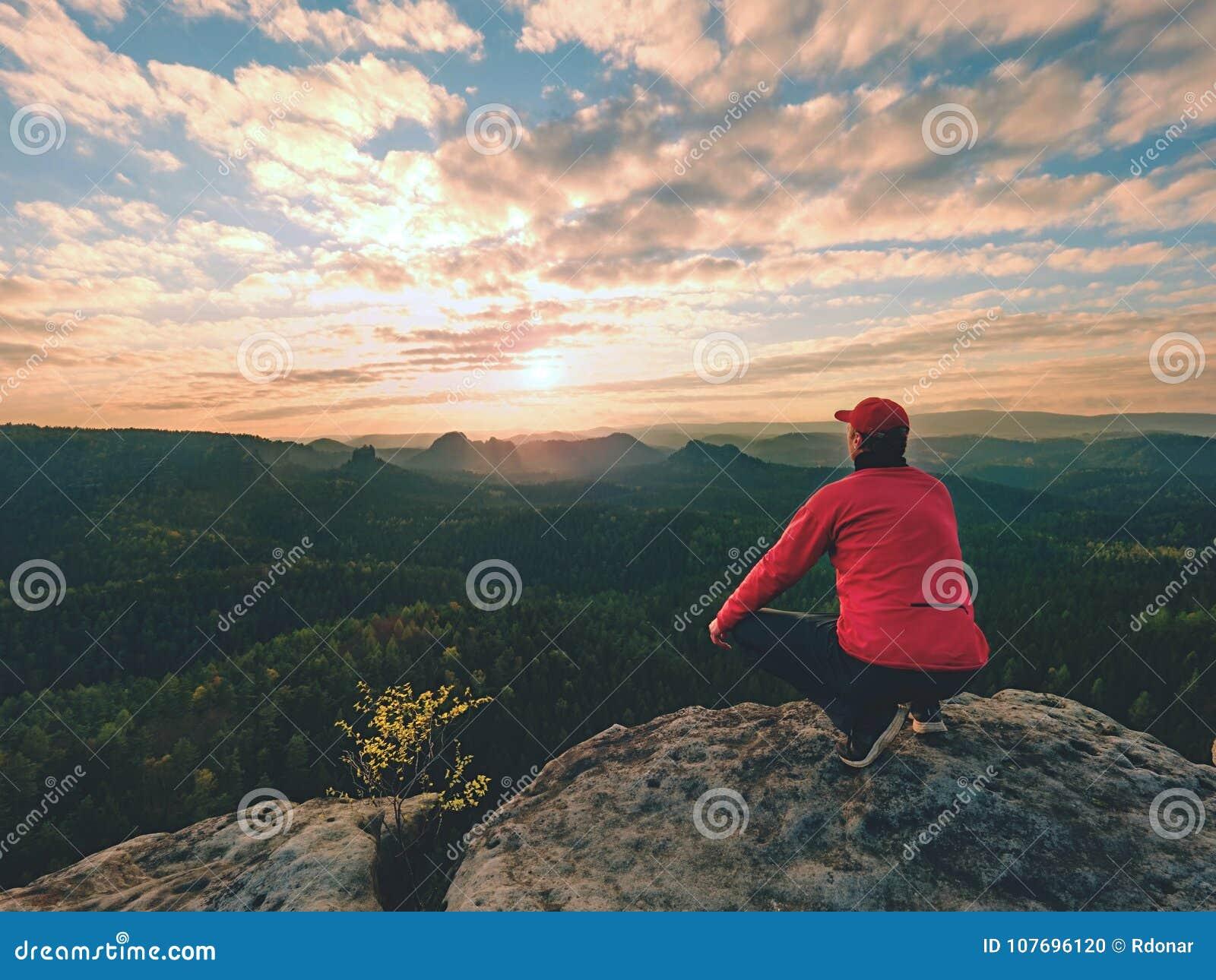 De wandelaarmens neemt een rust op bergpiek De mens legt op top,