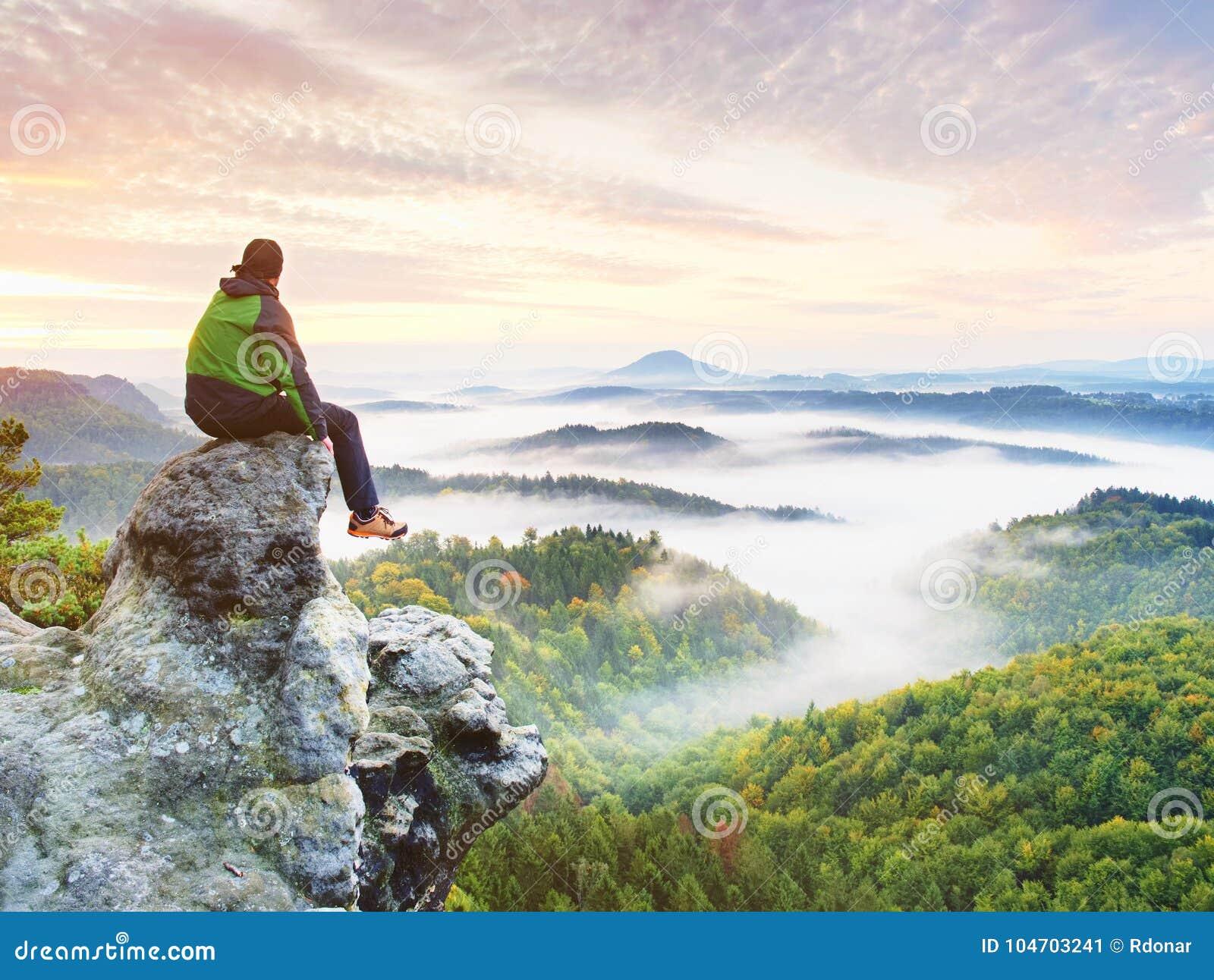 De wandelaarmens neemt een rust op bergpiek De mens zit op scherpe top en geniet van spectaculaire mening