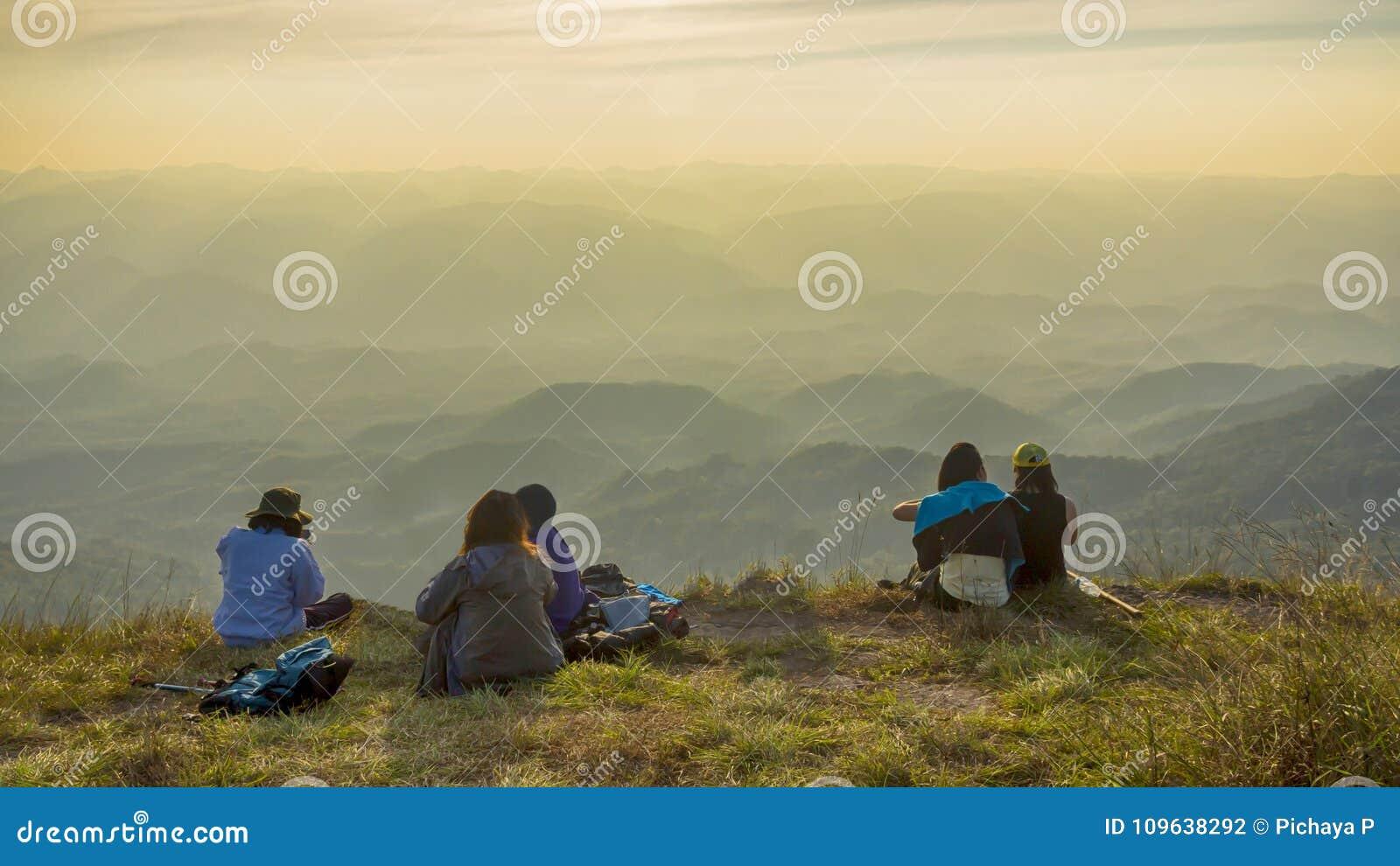 De wandelaarmensen nemen een rust en zitten op bergpiek met de herfstmo