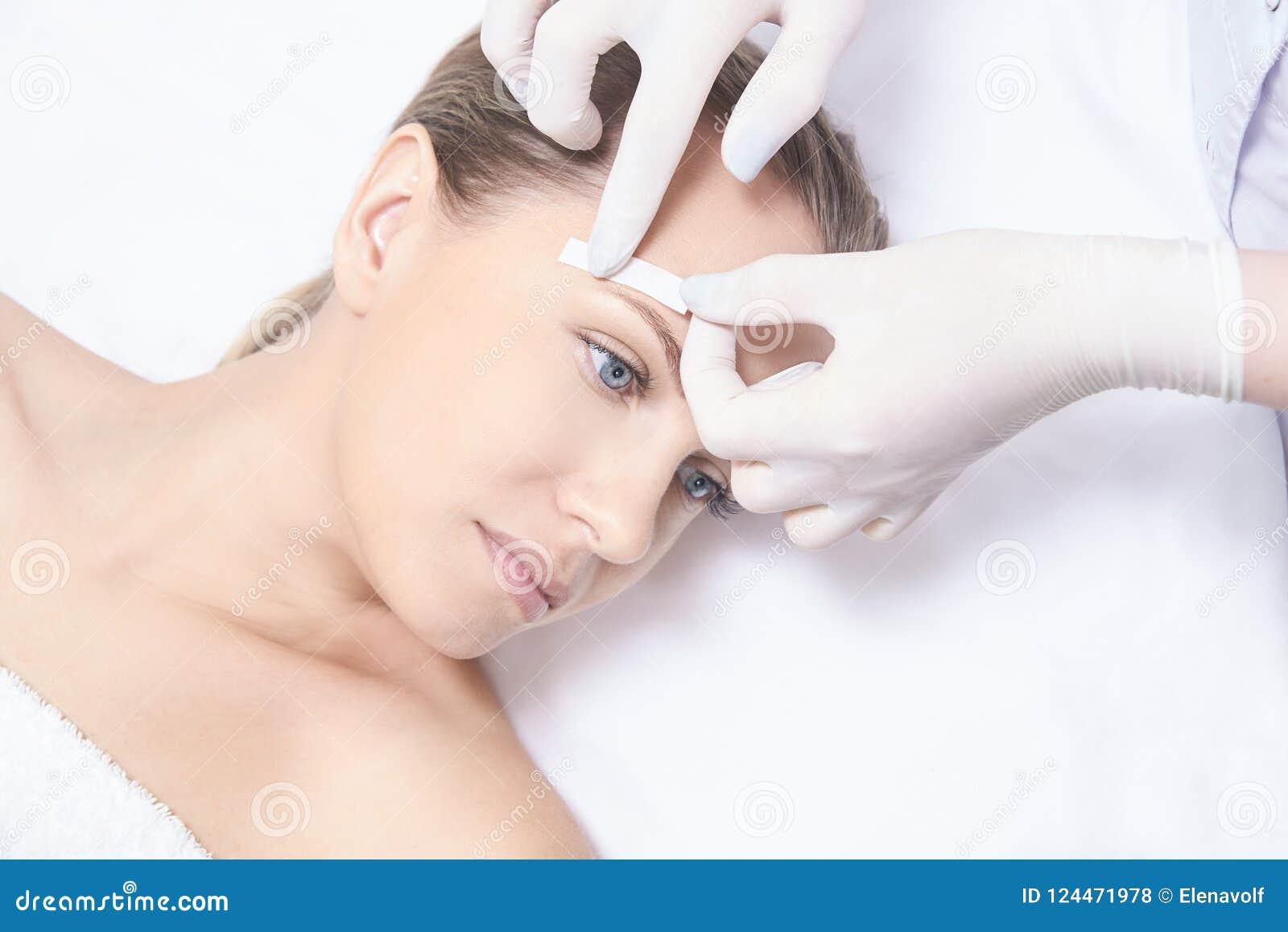 In de was zettend vrouwenlichaam De verwijdering van het suikerhaar epilation van de laserdienst De schoonheidsspecialistprocedur