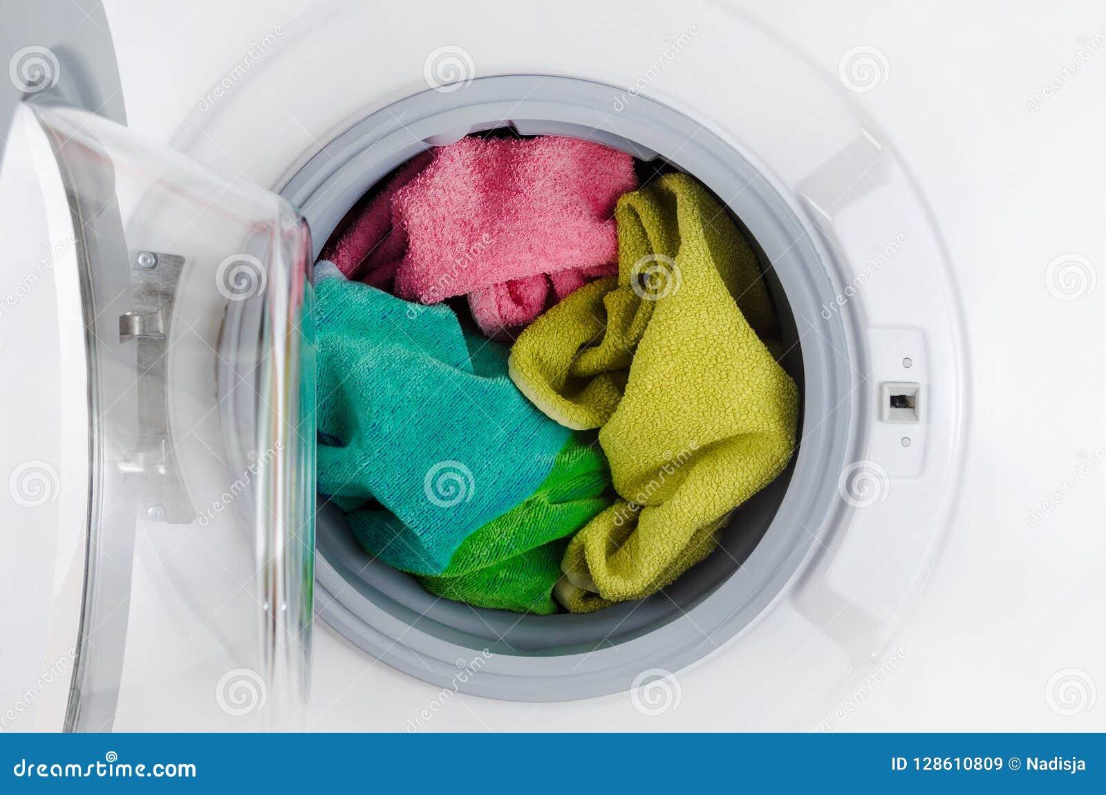 De wasmachine met kleurenhanddoeken, kleren, opent