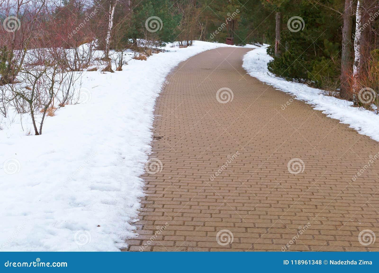 De weg van het bedekken plakken van sneeuw, sneeuw worden ontruimd smolt aan de vuile kant van de weg die
