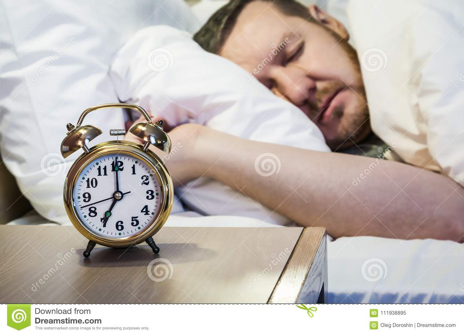 De wekker zich bevindt op een bedlijst in de ruimte of hotelruimte