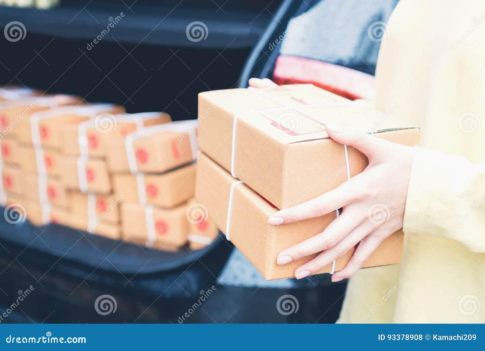 De werknemers houden een pakket in de auto naar de klant te verzenden Het online opdracht geven tot voor het gemak van klanten