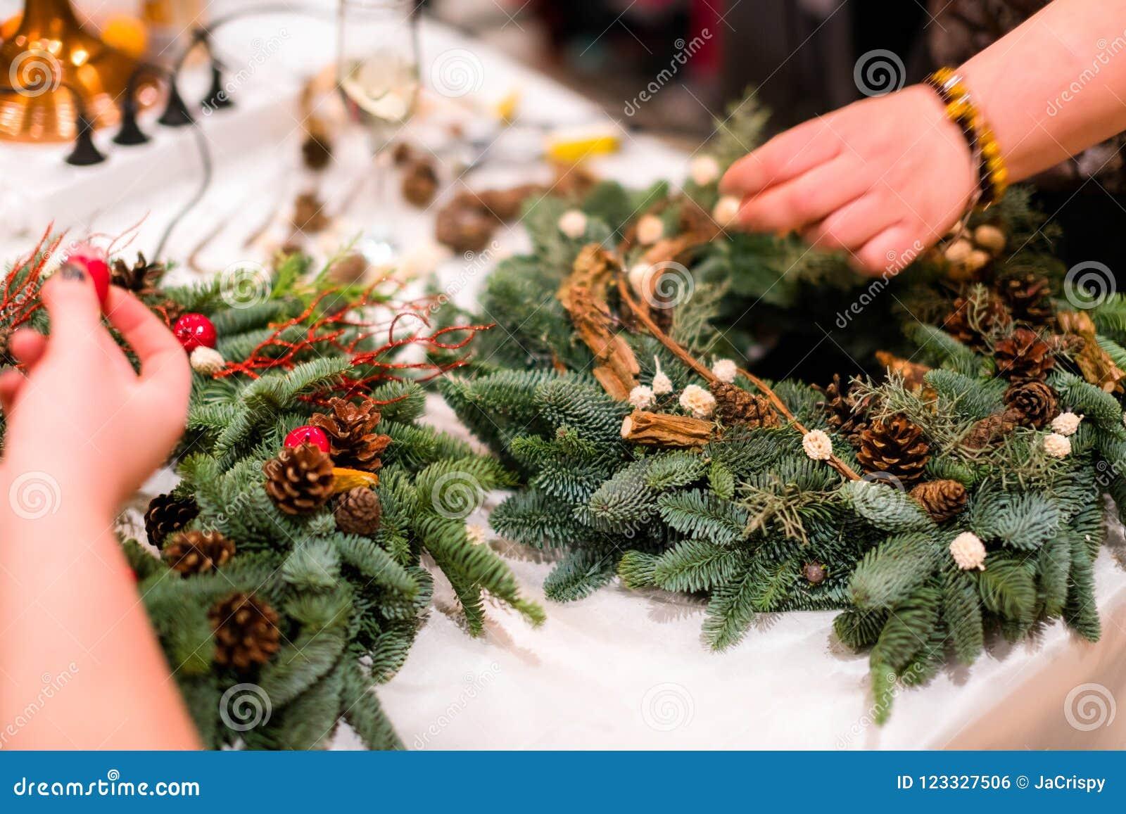 De wevende workshop van de Kerstmiskroon Vrouwenhanden die holida verfraaien