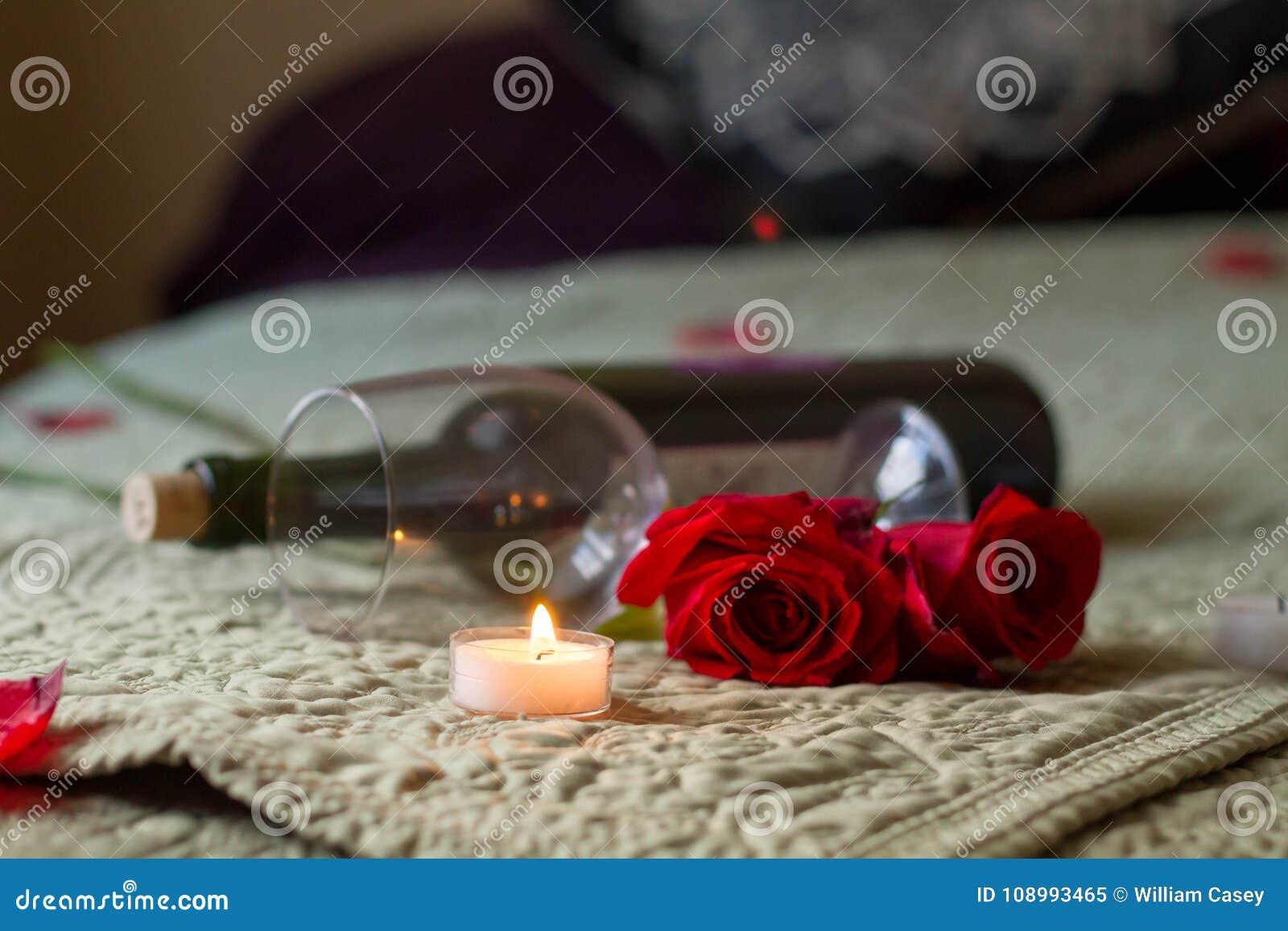 De Wijn en de rozen van de valentijnskaartendag op bed met theelicht
