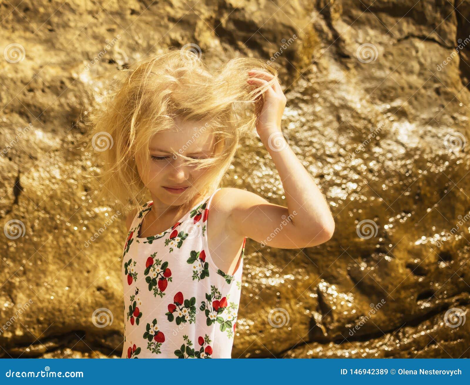 De wind speelt het haar in blond meisje op het strand