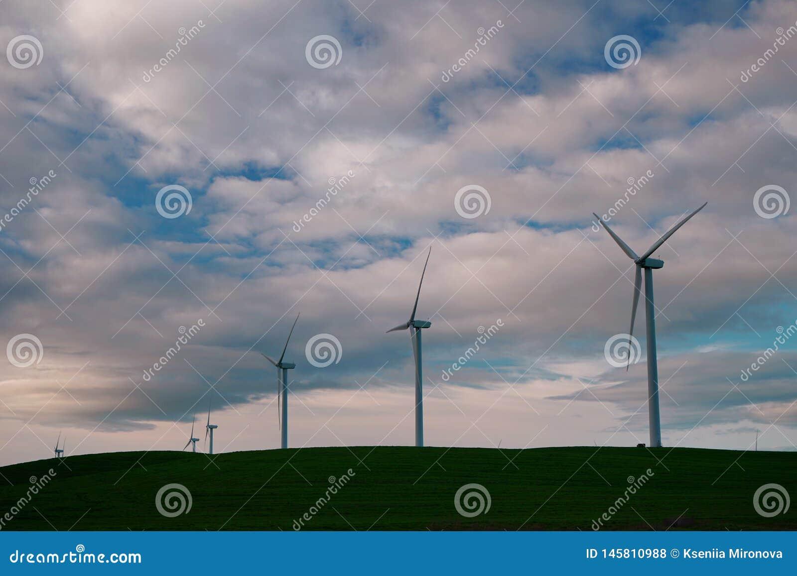 De windmolenturbines zijn close-up tegen de achtergrond van zonsondergangwolken