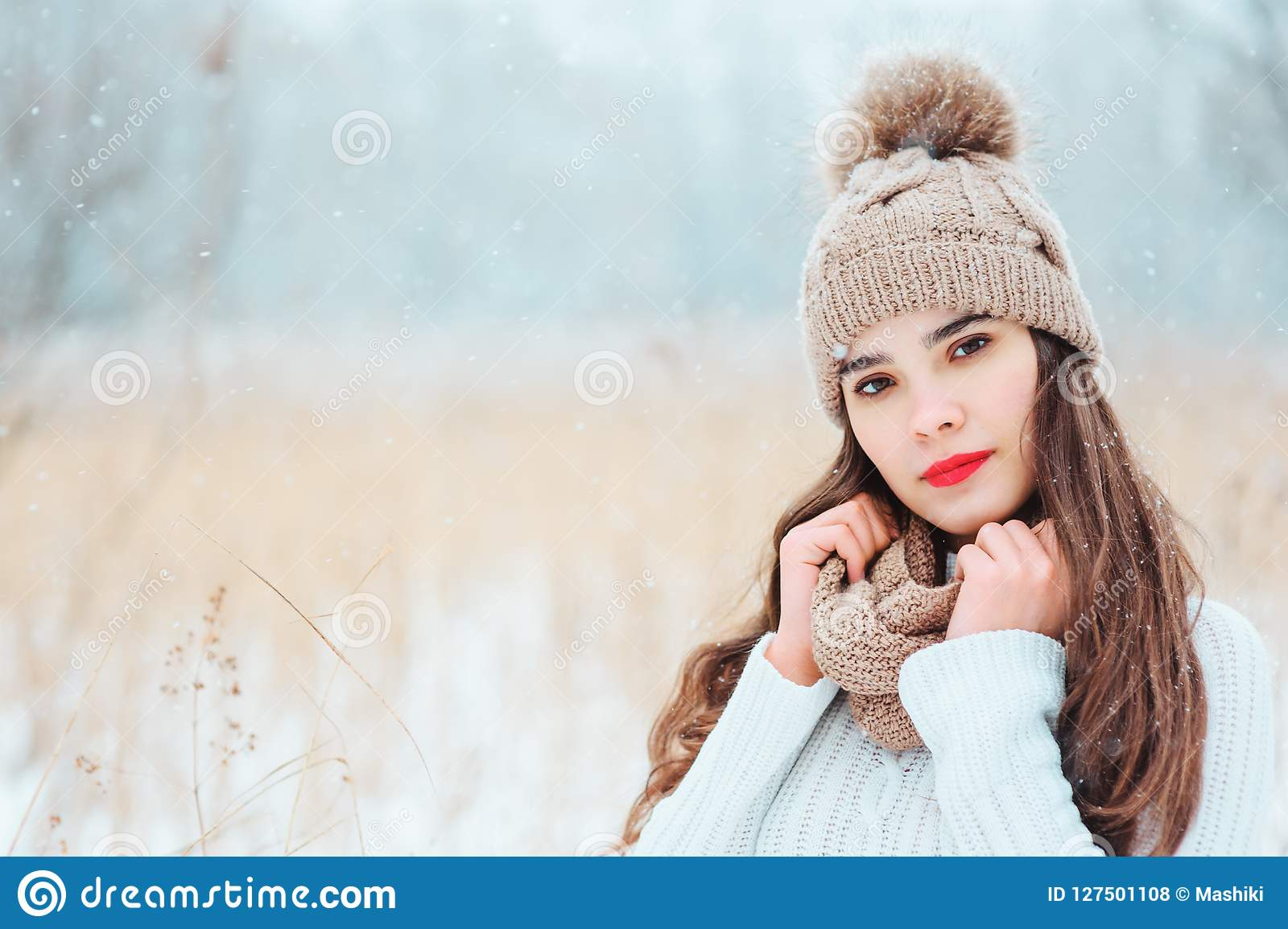De winter dicht omhooggaand portret van mooie glimlachende jonge vrouw in gebreide hoed en sweater die openlucht ondersneeuwval l