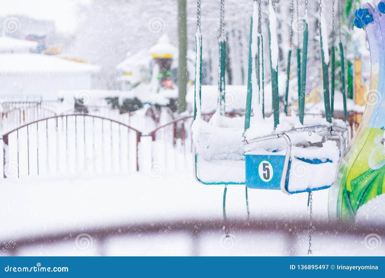 De Winter verlaten die park buiten het seizoen leeg en in sneeuw wordt behandeld Droevige foto s van Speelplaats in de winter met