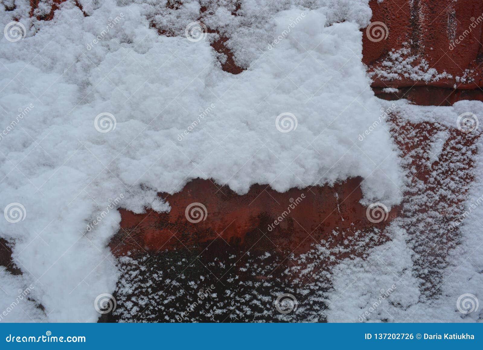 De winterachtergrond, aanhangende sneeuw, mooie besnoeiing van zware die sneeuw op een blad van de metaalbouw, met oude rode verf