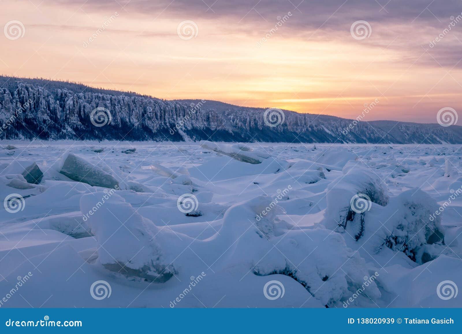 De winterlandschap in purpere tonen met geribbeld ijs op de bevroren rivier
