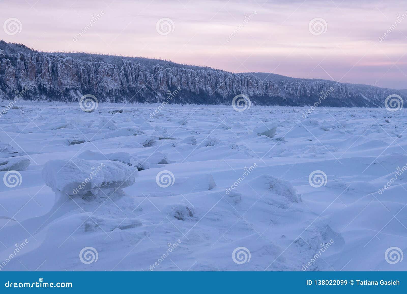 De winterlandschap in purpere tonen met geribbeld ijs op de bevroren rivier bij zonsondergang