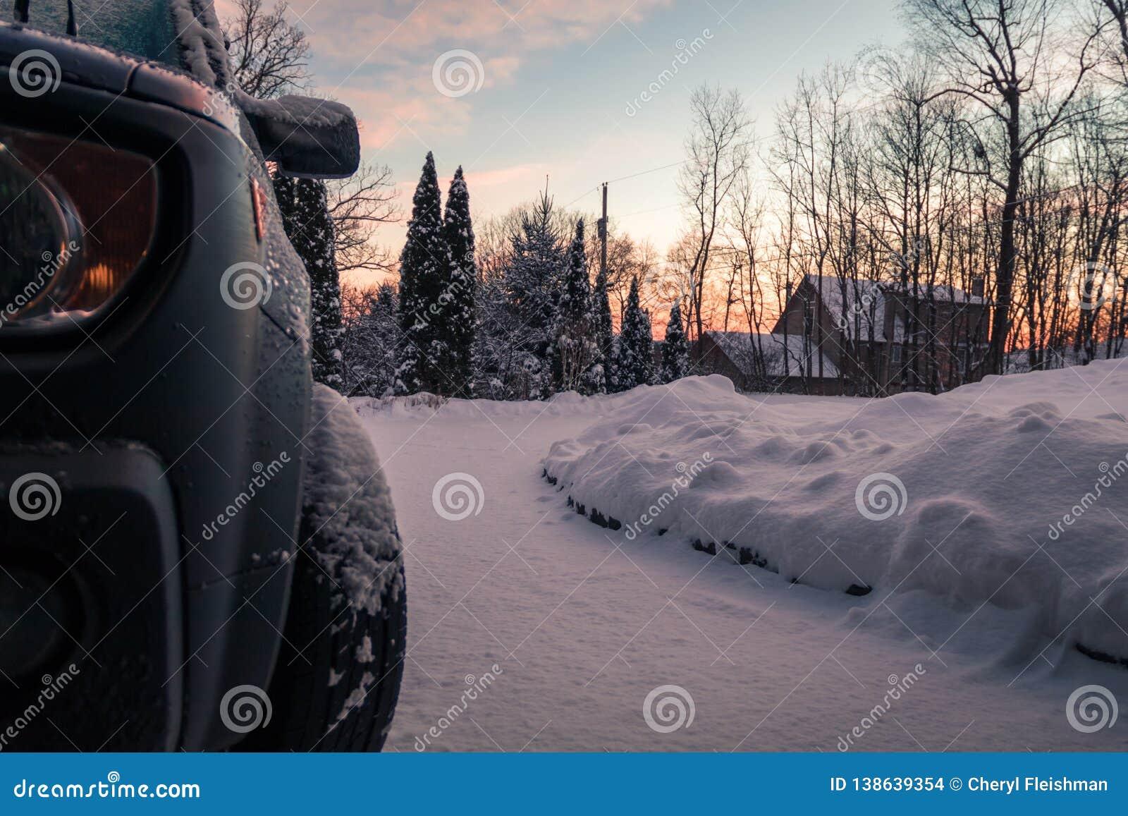 De de wintersneeuw bedekt oprijlaan en voertuig op een stille ochtend bij dageraad