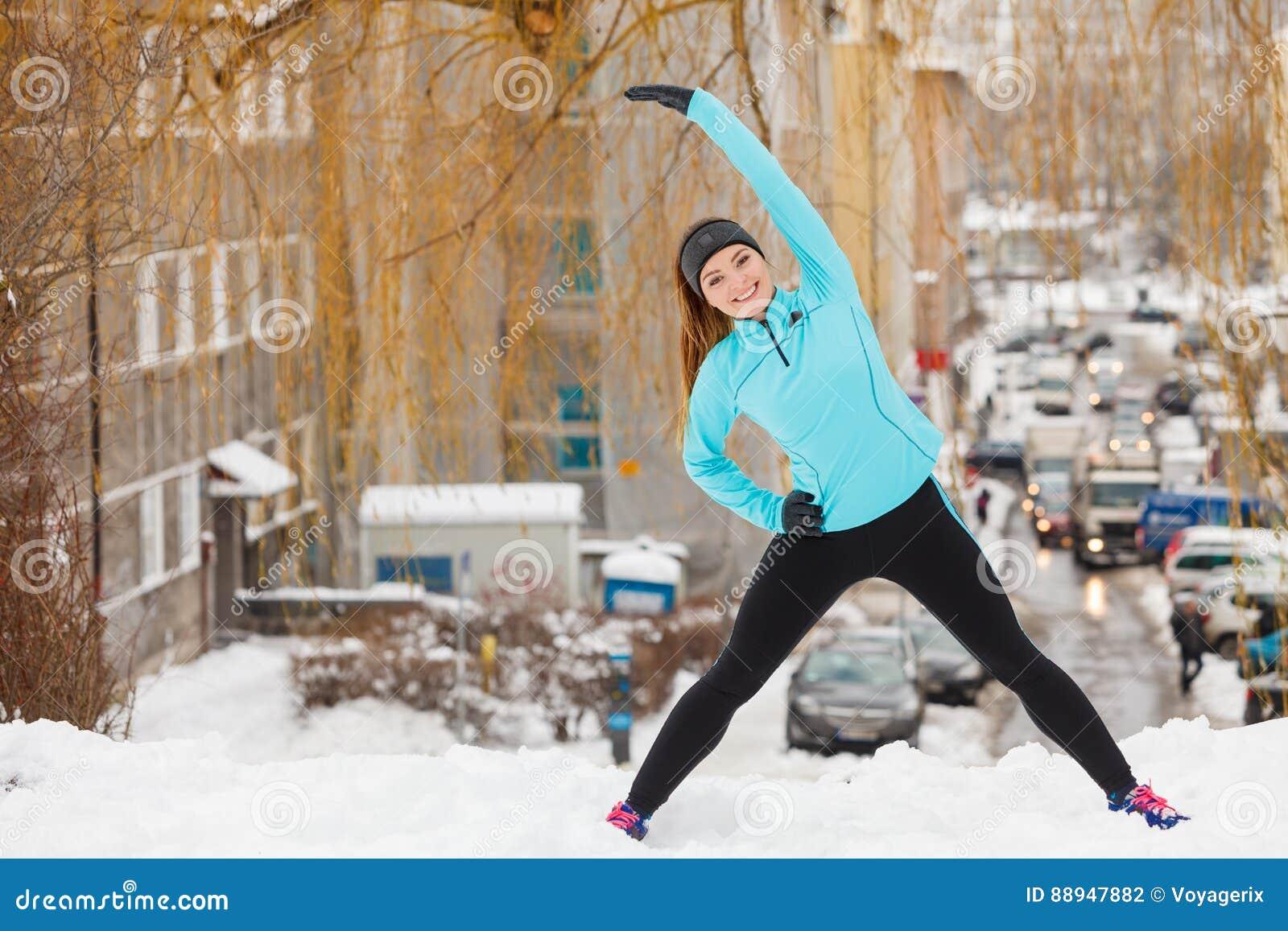 De wintertraining Meisje die sportkleding dragen, uitrekt oefeningen