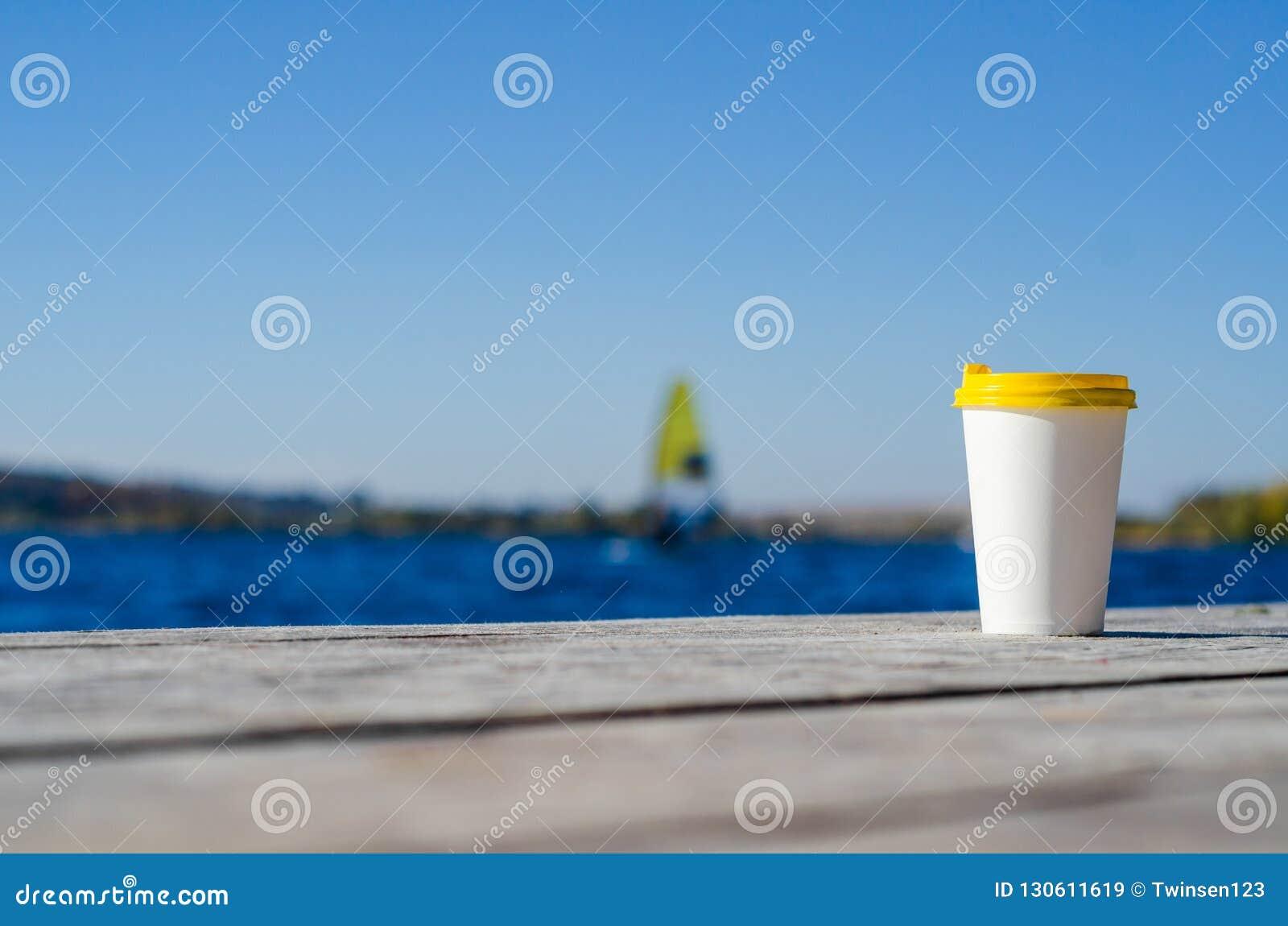 De Witboekkop met een geel plastic deksel bevindt zich op de raad op de kust van het meer