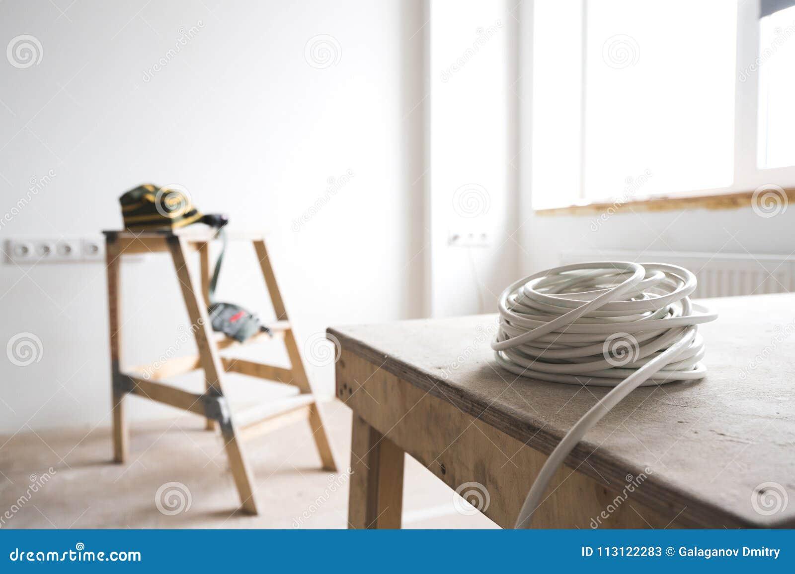 De witte elektrokabel rust op de ladder van de geit binnen de flat en de reparatie