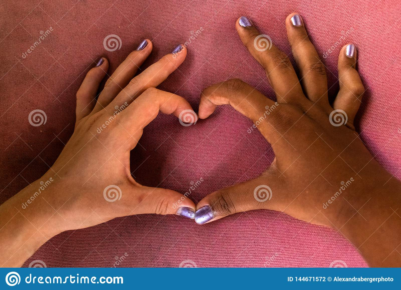 De witte en zwarte handen van meisjes vormen een hart van vingers tegen racisme