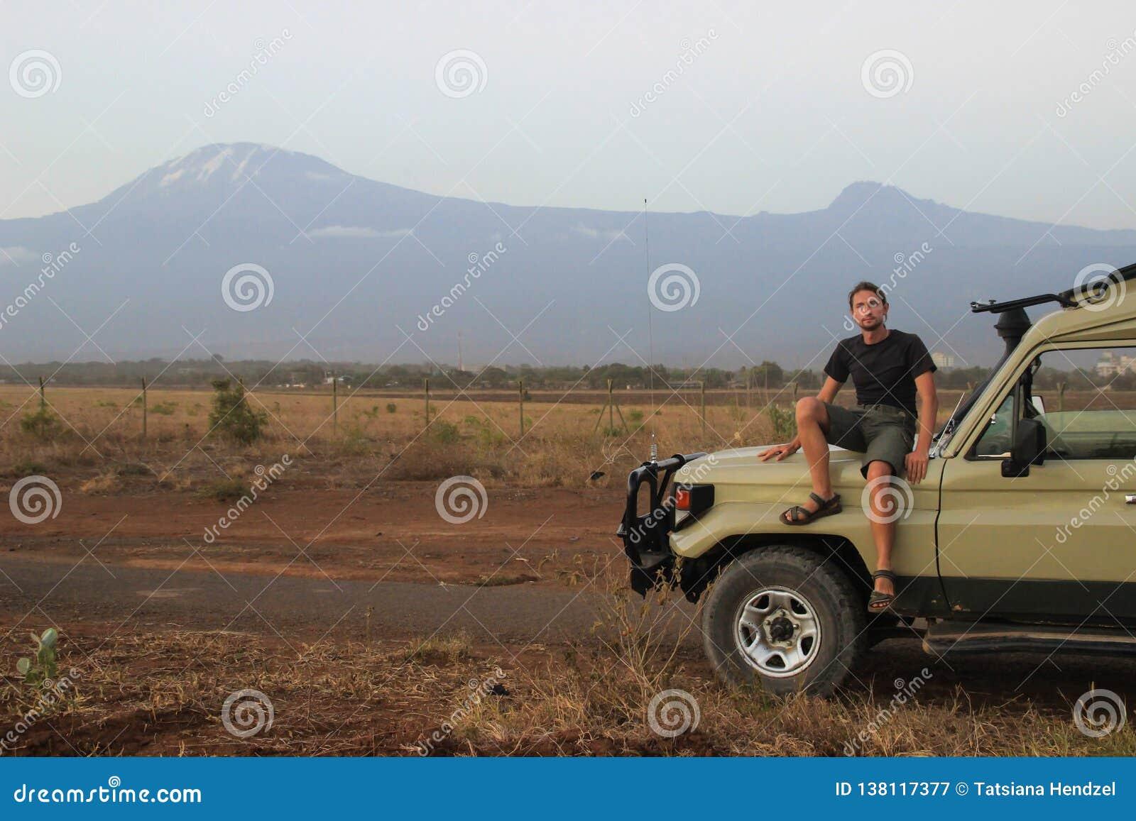 De witte Kaukasische reiziger in sportkleding zit in een jeep op de achtergrond van Onderstel Kilimanjaro