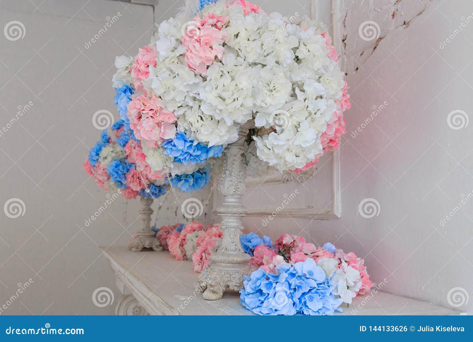 De witte open haard is verfraaid met kaarsen en bloemen