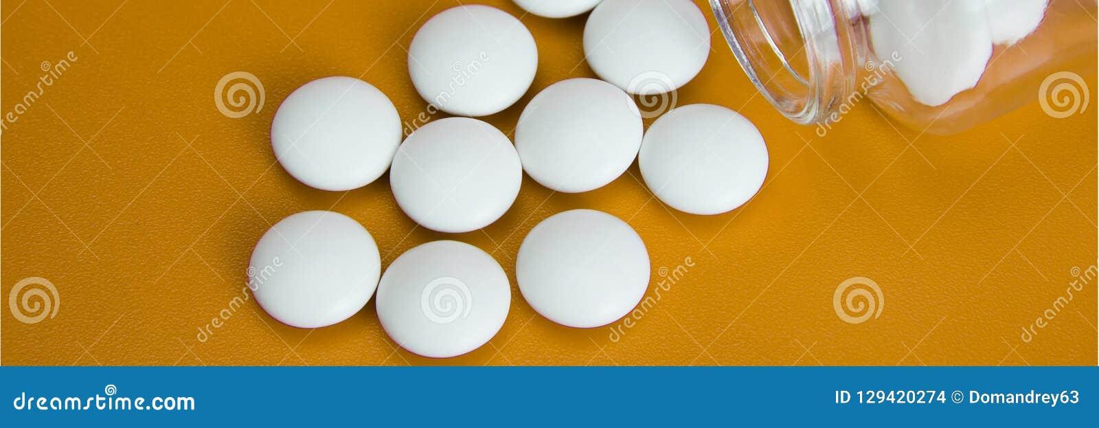 De witte tabletten zijn verspreid van een glasfles