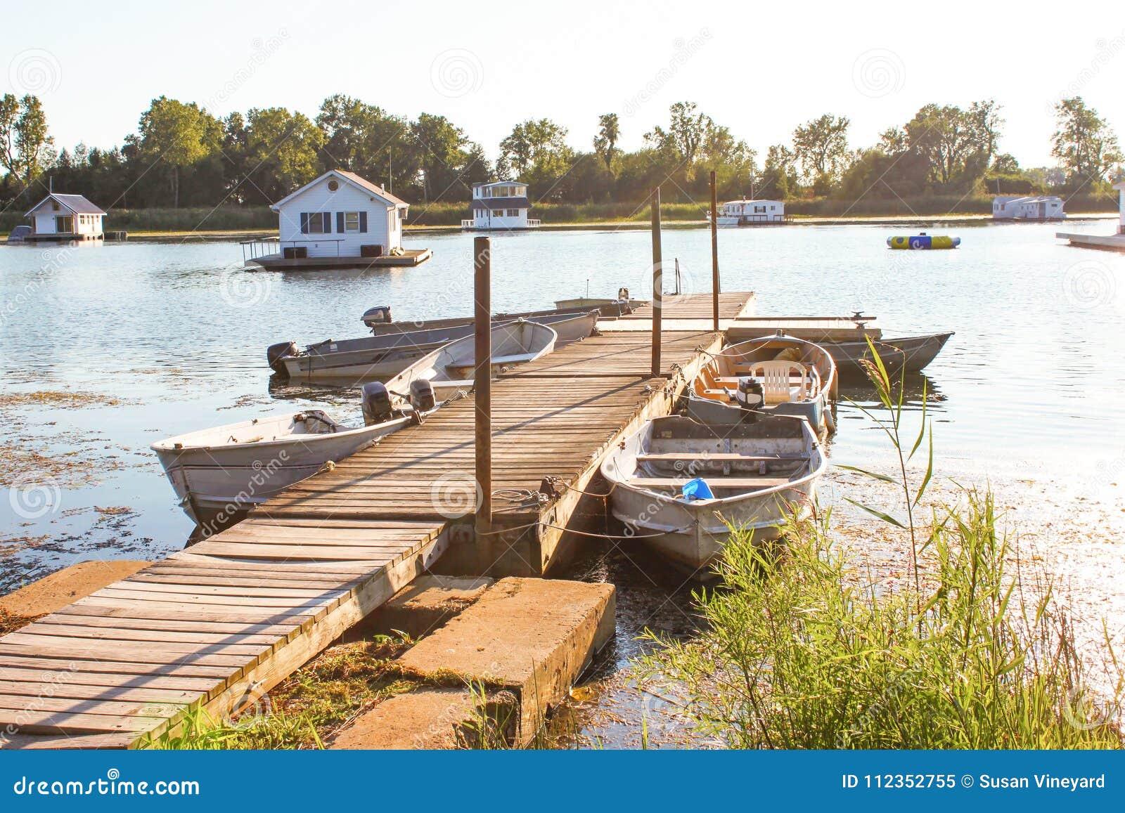 De woonboten in vijver op Meer Erie van dok met roeiboten verbonden om tot hen bij gouden uur op een de zomerdag toegang te hebbe