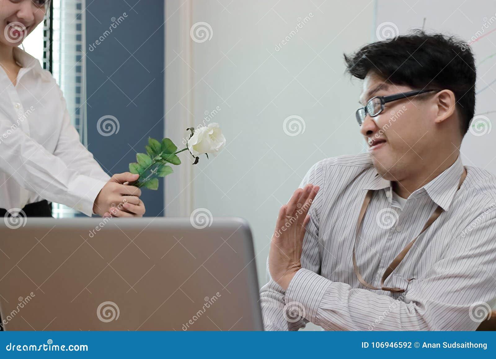 De zachte nadruk boze Aziatische bedrijfsman weigert witte rozen van aantrekkelijke vrouw Teleurgesteld liefdeconcept
