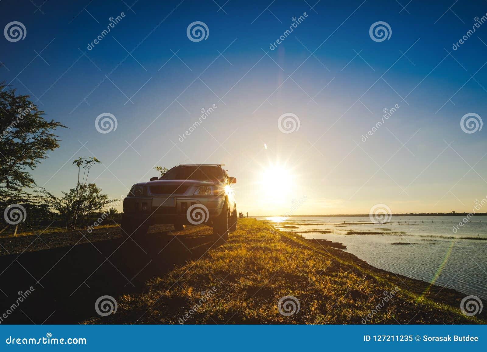 De zakenlieden met SUV-auto s parkeerden op de weg langs het reservoir Het letten van de op Zonsondergang
