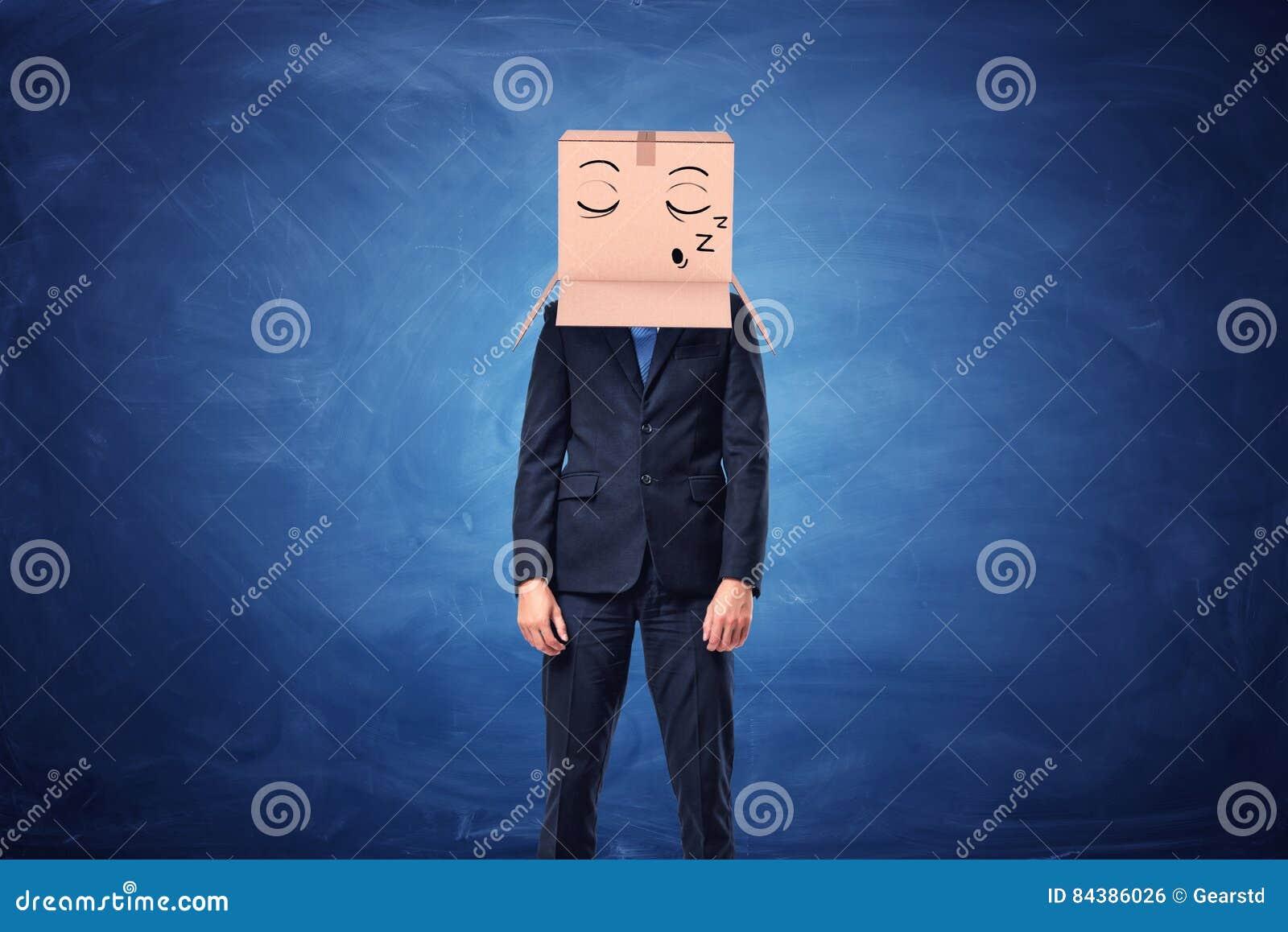 De zakenman draagt kartondoos op hoofd met slaperig gezicht
