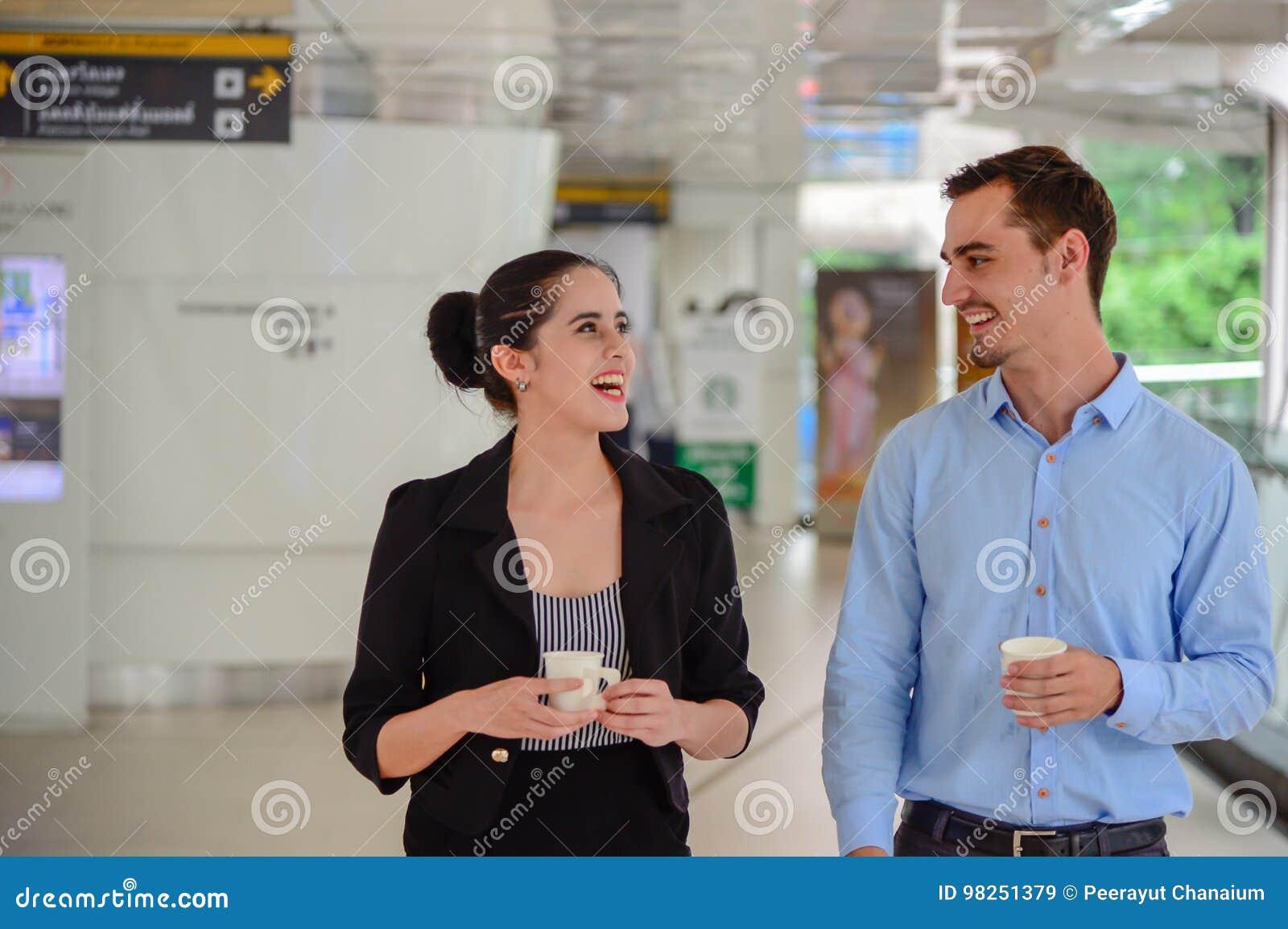De zakenman en de onderneemster bevinden zich en lachend, bespreking over zaken met Plastic Mok op hand