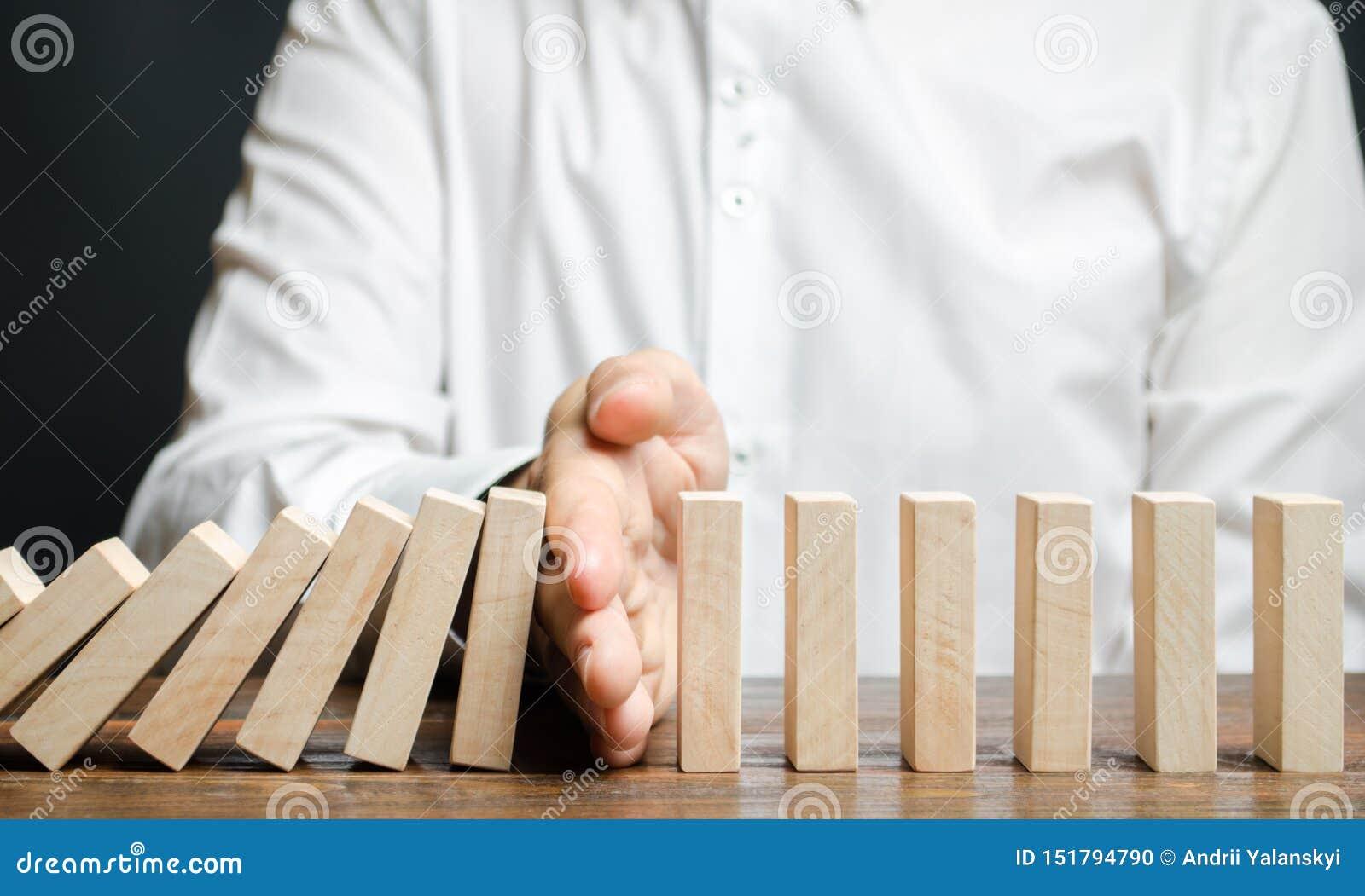 De zakenman houdt domino het vallen tegen Risicobeheerconcept Het succesvolle sterke bedrijfs en probleem oplossen Betrouwbare le