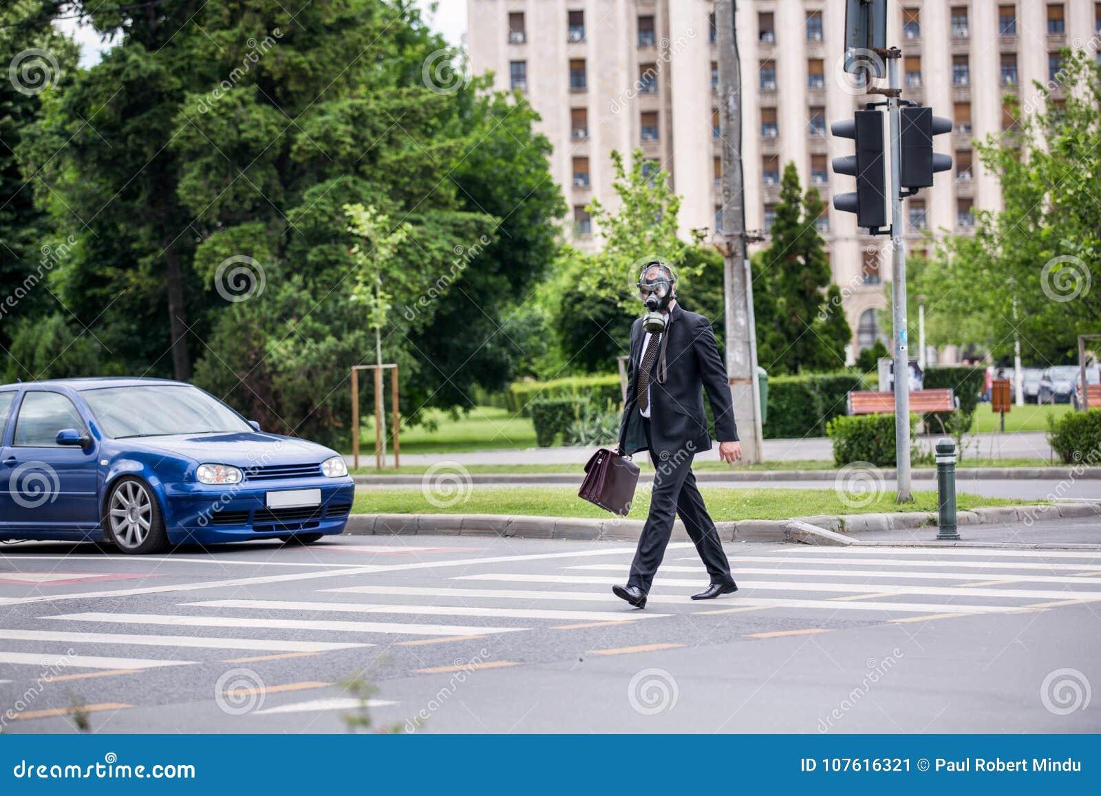 De zakenman kruist de straat openlucht met aktentas die een gasmasker dragen
