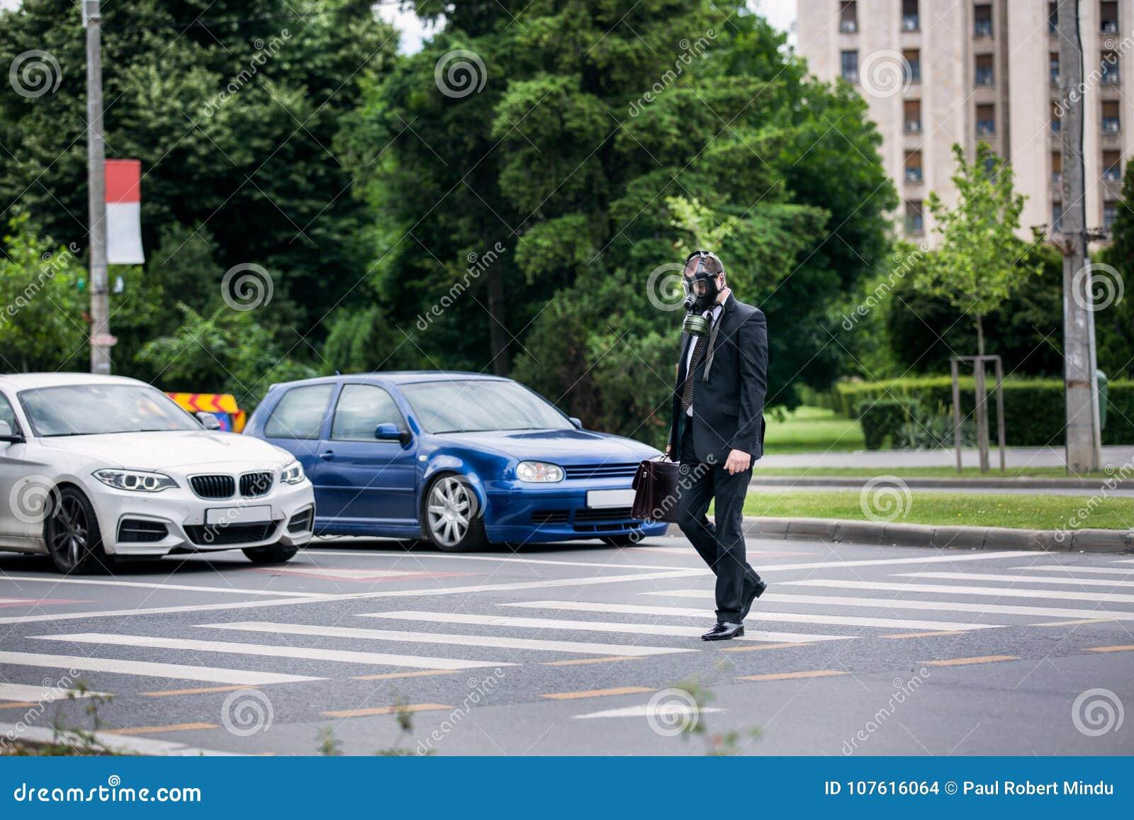 De zakenman kruist de straat openlucht met aktentas die een gasmasker op het gezicht dragen