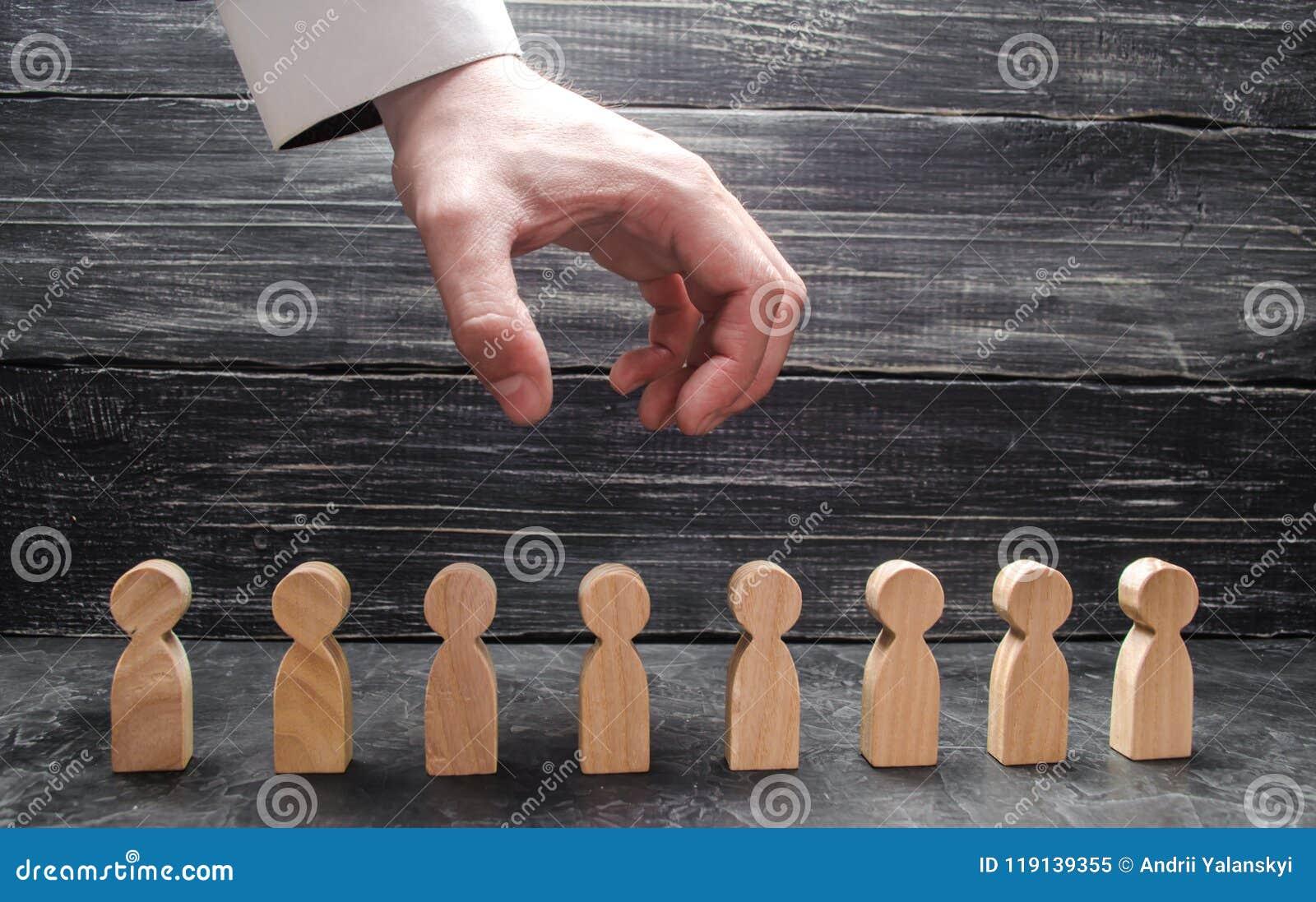 De zakenman` s hand hangt over de cijfers van mensen en bereidt hen voor om te grijpen Het ontslag van arbeiders, de vernietiging