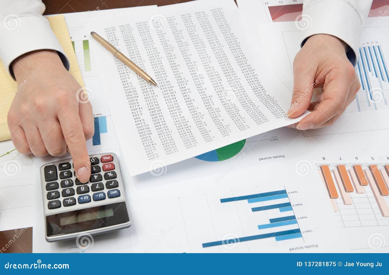 De zakenman van de werkplaats Contracten, grafieken, en grafieken op het bureau