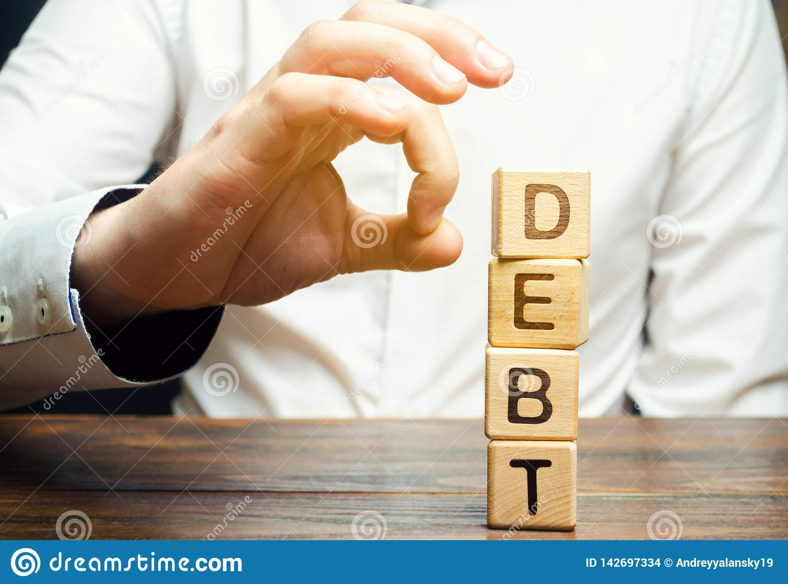 De zakenman verwijdert houten blokken met de woordschuld Vermindering of het herstructureren van schuld Faillissementsaankondigin