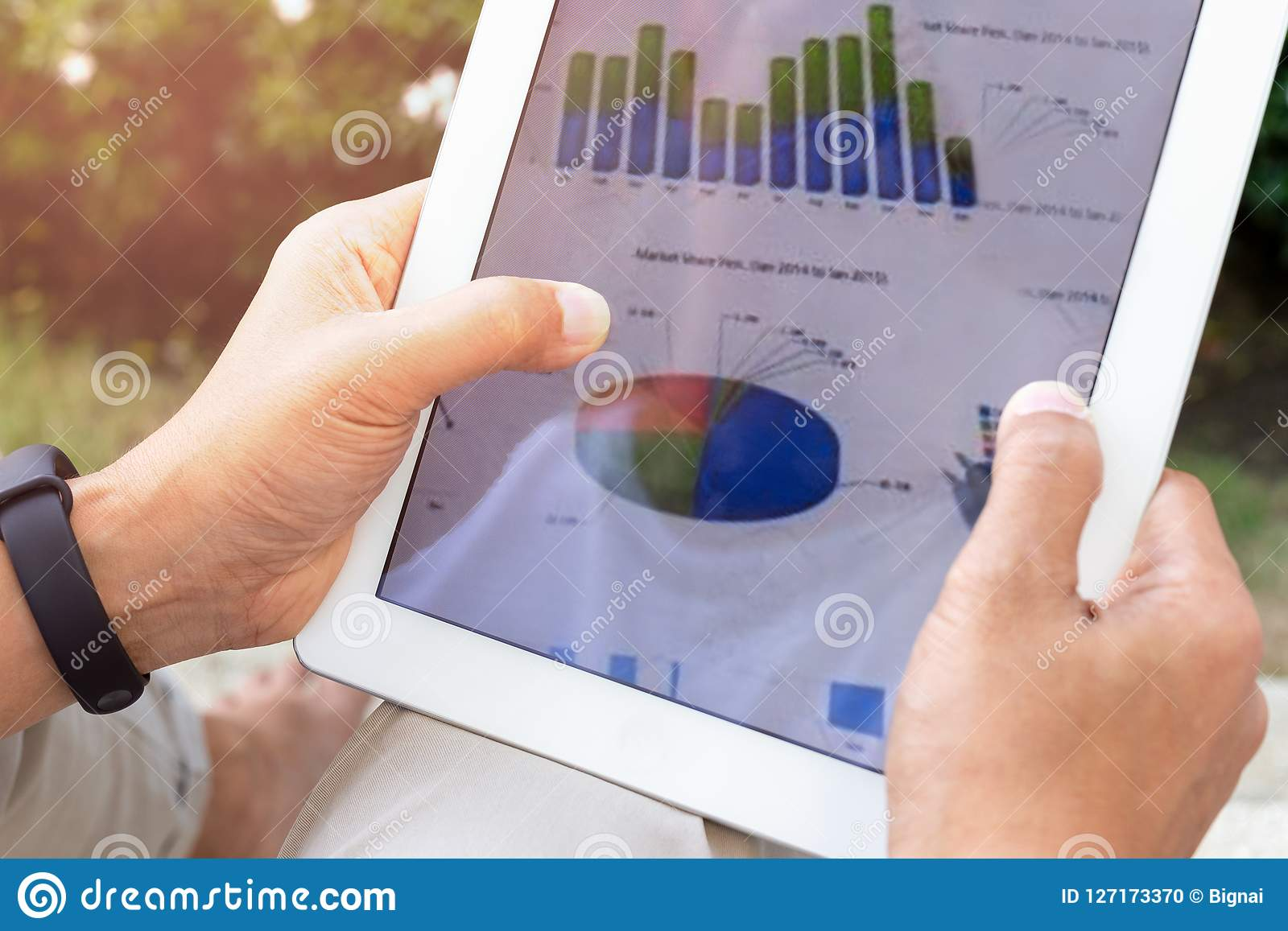 De zakenmanhanden die het tabletscherm met behulp van tonen groene grafiek terwijl wor