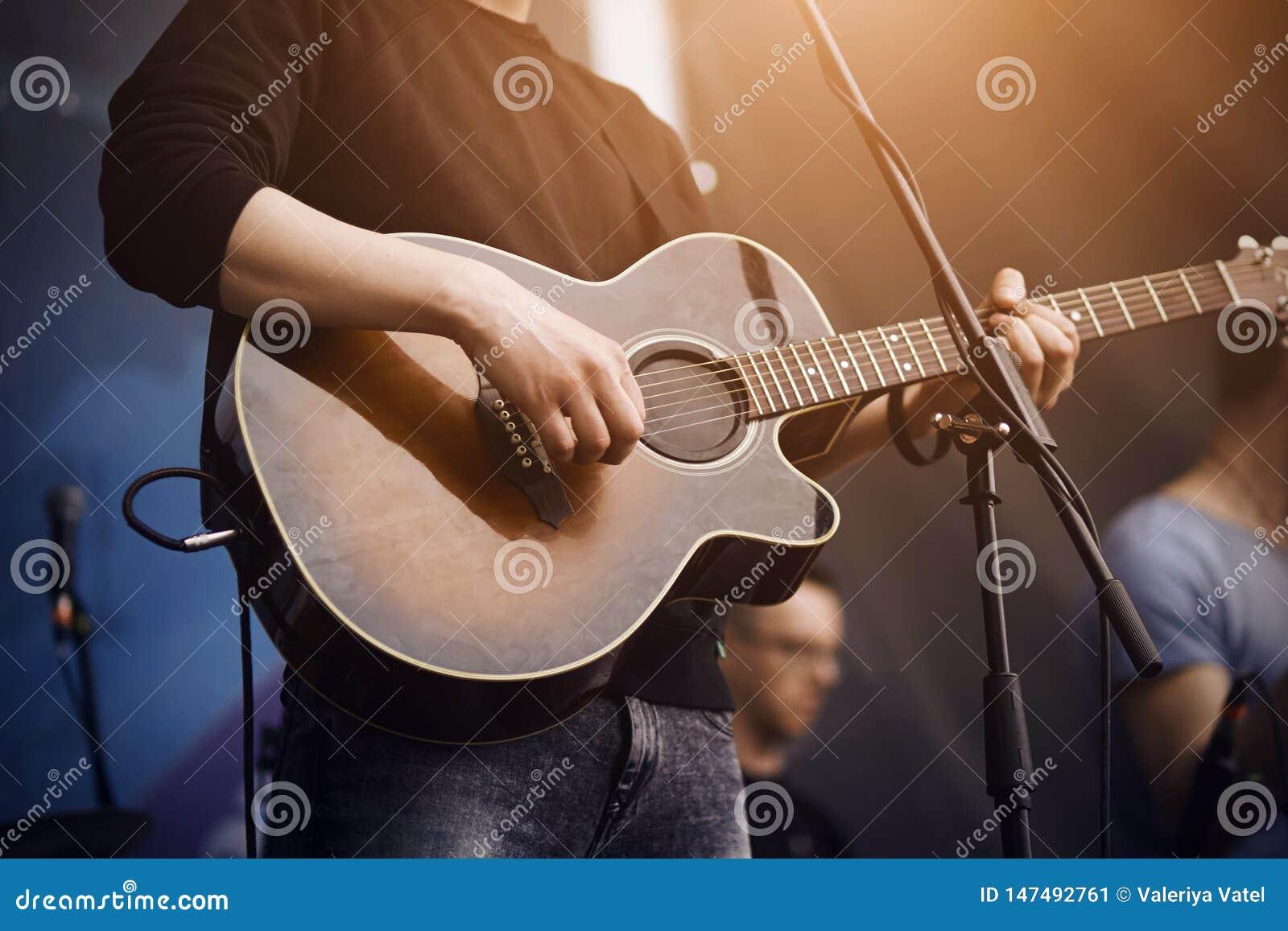 De zanger speelt een gitaar van donkere kleur