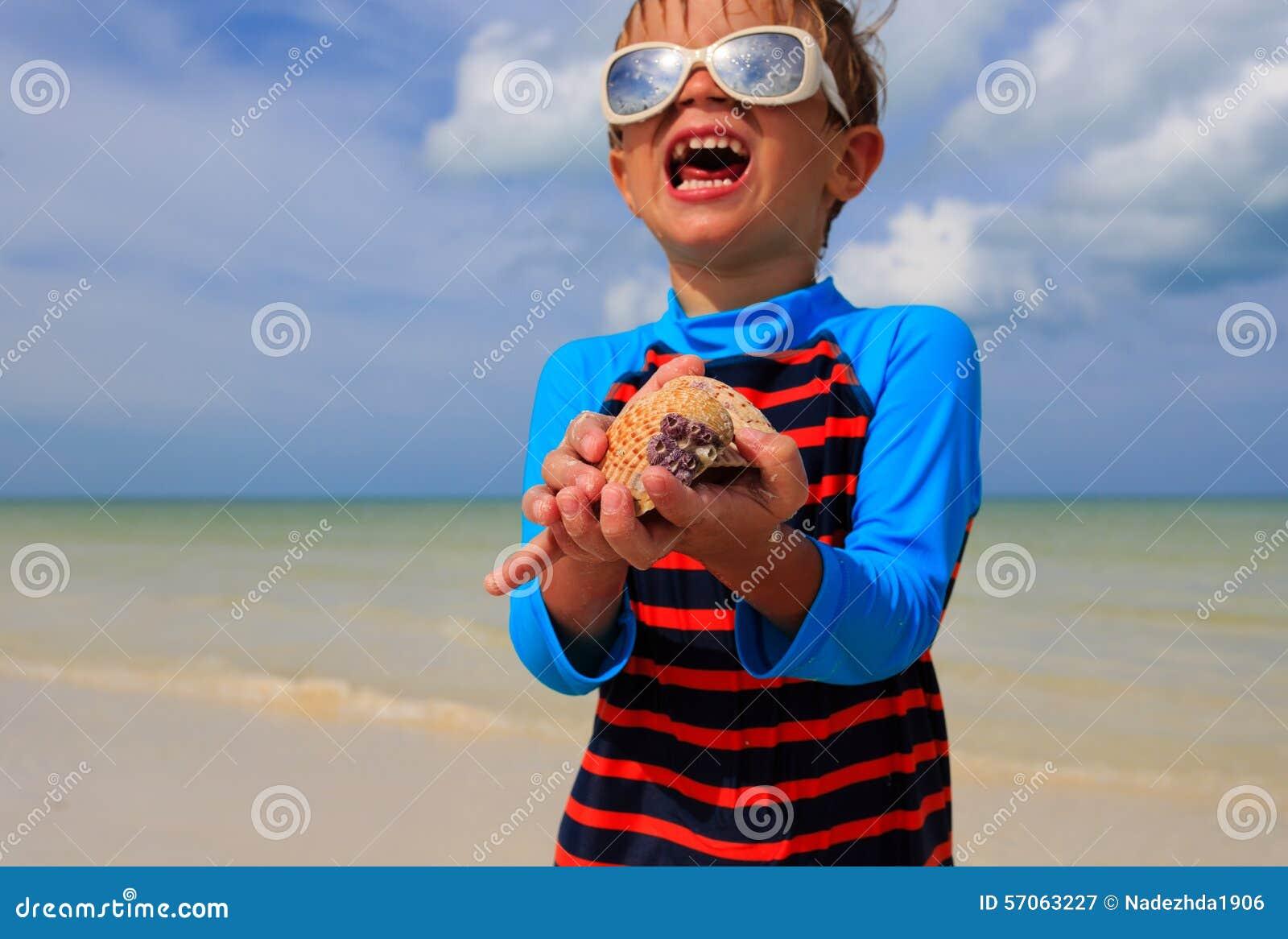 De zeeschelpen van weinig jongensholding op de zomerstrand