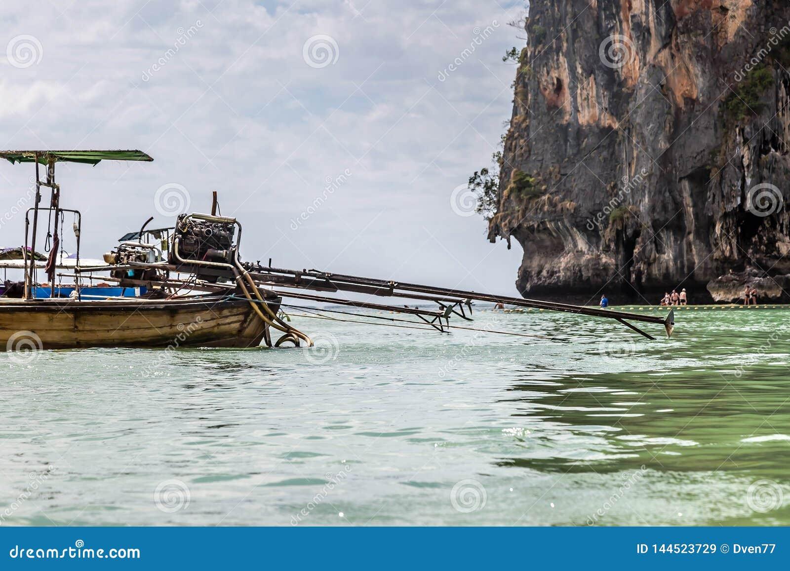 De zelf-gemaakte motor van de pick-up wordt opgezet op een motorboot met lange staart tegen de achtergrond van een zandig strand