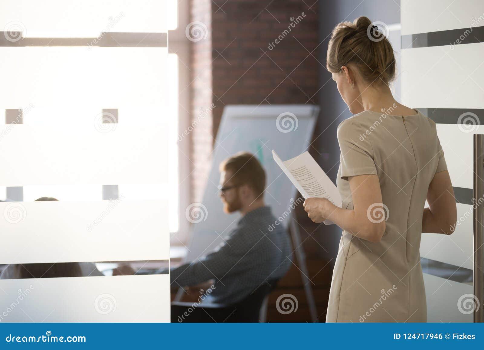 De zenuwachtige vrouwelijke doen schrikken werknemer sluit zich aan team bij vergadering in bureau